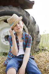 Porträt des lächelnden kleinen Jungen auf einem Strohballen mit Strohhut