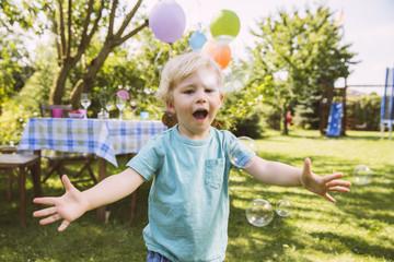 Junge versucht, Seifenblasen im Garten zu fangen