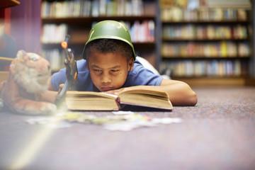 Junge mit Helm und Gewehr liest Buch in der Bibliothek