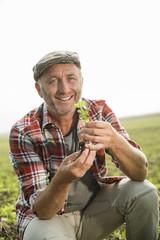 Der lächelnde Bauer hält eine Pflanze auf einem Feld