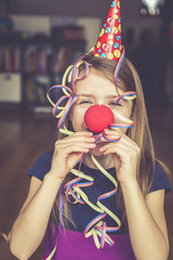 Kleines Mädchen mit Clownsnase und Kappe