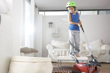 Junge im Wohnzimmer in Staubsauger verheddert