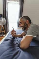 Lächelnder Mann auf seinem Bett, Blick auf seine Smartphone
