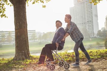 Enkel schiebt älteren Mann im Rollstuhl