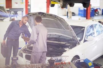 Automechaniker mit Kunden in Werkstatt