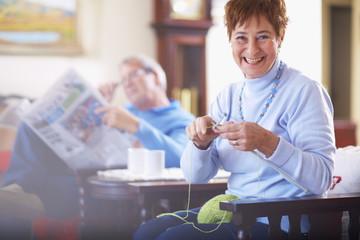 Ältere Frau beim Stricken, Mann im Hintergrund liest Zeitung