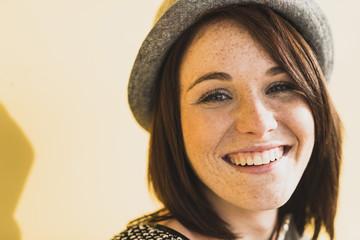 Porträt der lächelnden jungen Frau mit Hut