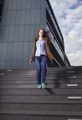 Porträt der lächelnden jungen Frau, geht die Treppe hinunter