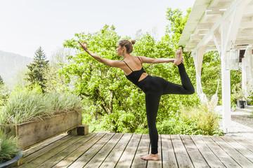 Frau praktiziert Yoga auf Holzterrasse