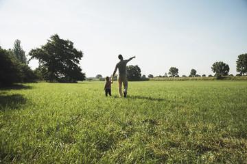 Vater zu Fuß mit seiner kleinen Tochter auf einer Wiese
