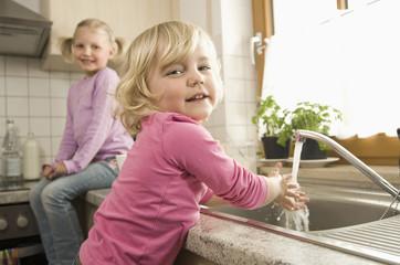 Mädchen beim Hände waschen, Schwester im Hintergrund