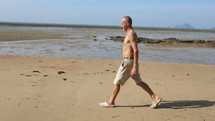 old man of athletic build starts to jog along sand beach