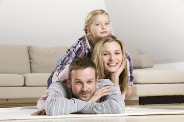 Eltern und Tochter (3-4) entspannen zu Hause