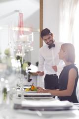 Kellner serviert Abendessen im eleganten Restaurant
