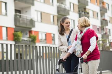 Erwachsene Enkelin hilft ihrer Großmutter zu Fuß mit Rollator