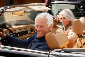 Porträt, lächelndes älteres Paar sitzt in einem Cabrio