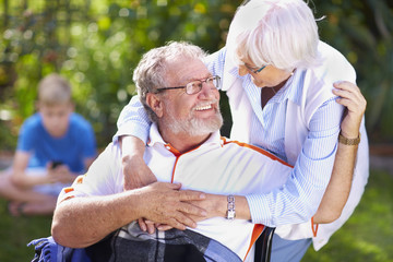 Ältere Frau umarmt Mann im Rollstuhl