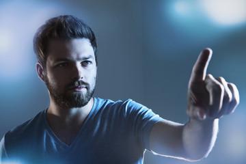 Mann zeigt auf imaginären Touchscreen