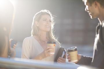 Drei Menschen mit Kaffee zum Mitnehmen