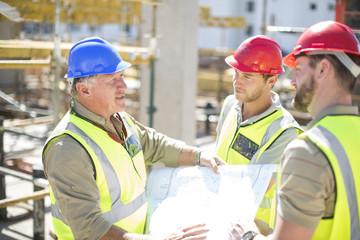 Bauarbeiter diskutieren Baupläne auf der Baustelle