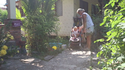 grandmother seats blonde girl toddler into pram and fasten belts