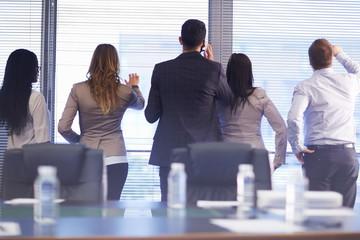 Gruppe von Geschäftsleuten, Blick durch Jalousien in Besprechungszimmer
