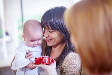 Mutter mit Baby und Freundin, begutachten Baby-Schuhe