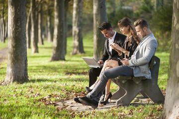 Drei Geschäftsleute, die auf einer Parkbank sitzt mit Laptop, Smartphone und Tablet-PC