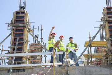 Bauarbeiter diskutieren Baupläne auf Baustelle