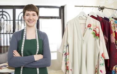 Porträt der lächelnden Mode-Designerin mit Schürze und Maßband in ihrem Atelier