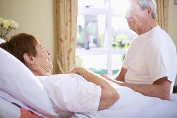 Ältere Frau im Krankenhausbett, im Gespräch mit älterem Mann