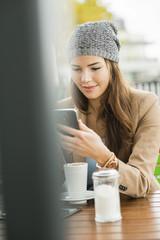 Junge Frau sitzt im Café mit Tablet - PC und liest SMS