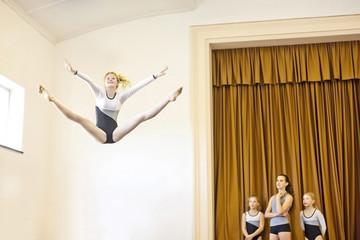 Mädchen im Gymnastik-Outfit springt in die Luft