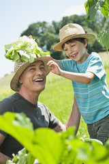 Deutschland, Bayern, Großvater mit Enkel im Gemüsegarten, lächelnd
