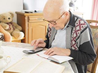 Alter Mann sitzt am Tisch auf der Suche nach Telefonnummer