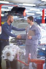 Automechaniker und Kunde, Händeschütteln in Werkstatt
