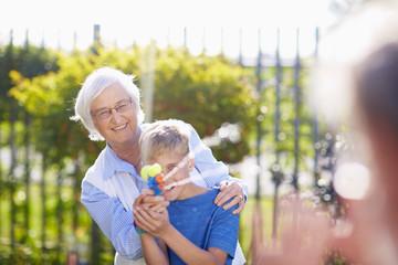 Enkel und Großmutter bespritzen Großvater mit Wasserpistole