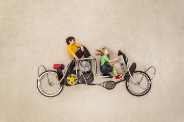 Kinder fahren in seltsamen Fahrzeugen