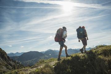 Österreich, Tirol, Tannheimer Tal, junges Paar wandert auf Höhenweg