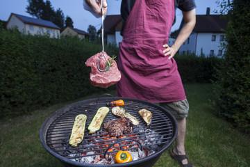 Deutschland, Bayern, Mann hält Grillfleisch mit einer Zange
