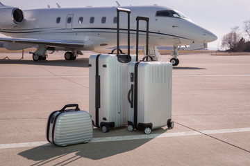 luggage in front of a corporate jet airplane