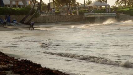 People play in ocean water on tropical island beach