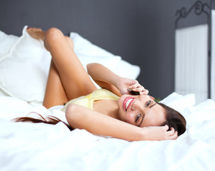 Cheerful casual young woman using mobile phone in bed at home