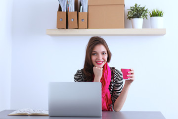 Portrait of a smiling businesswoman with coffee cup in front