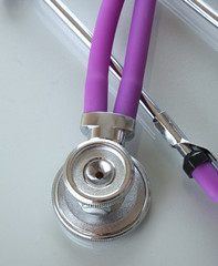 Stethoscope lying at the desk on white, closeup