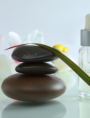bottles of essential oil and set  stones with flower