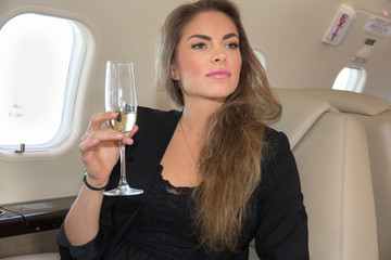 woman in a corporate jet drinking a glass of champagne