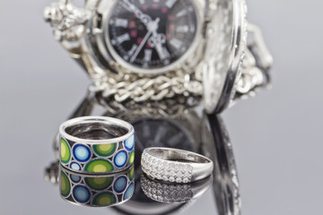 silver ring with stones and a ring with a colored ceramic enamel