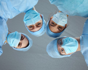 Surgeons team, wearing protective uniforms,caps and masks