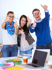 Young business people standing at office near desk and showing
